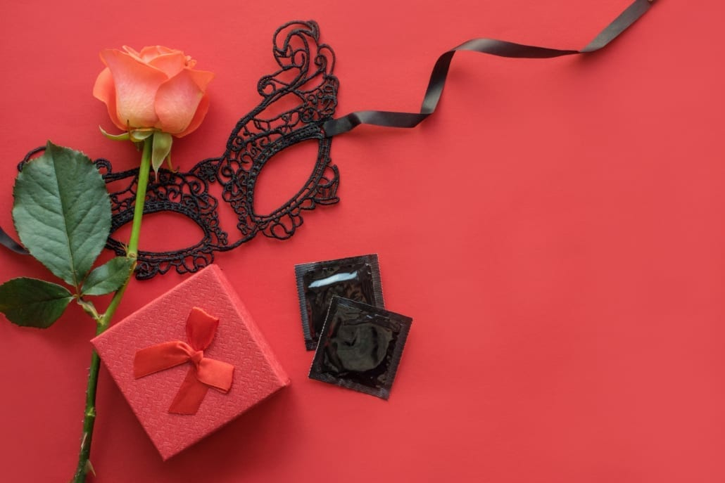 Love, passion, sex romance flat lay, mock up with red rose, black lace carnival mask, gift box and two condoms on red background. Safe sex, dating concept. Top view