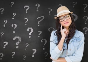 Portrait of a thoughtful woman in straw hat standing in front of chalkboard with question marks